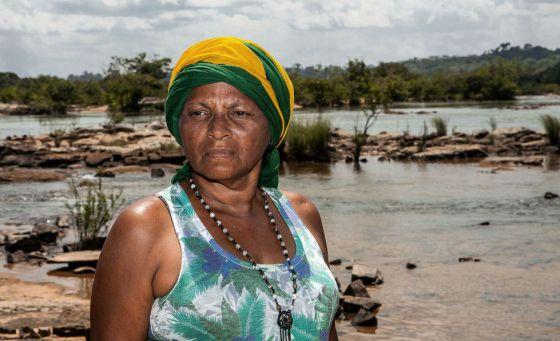 Raimunda, no rio, com uma bandeira do Brasil na cabeça porque diz que o país também é dela