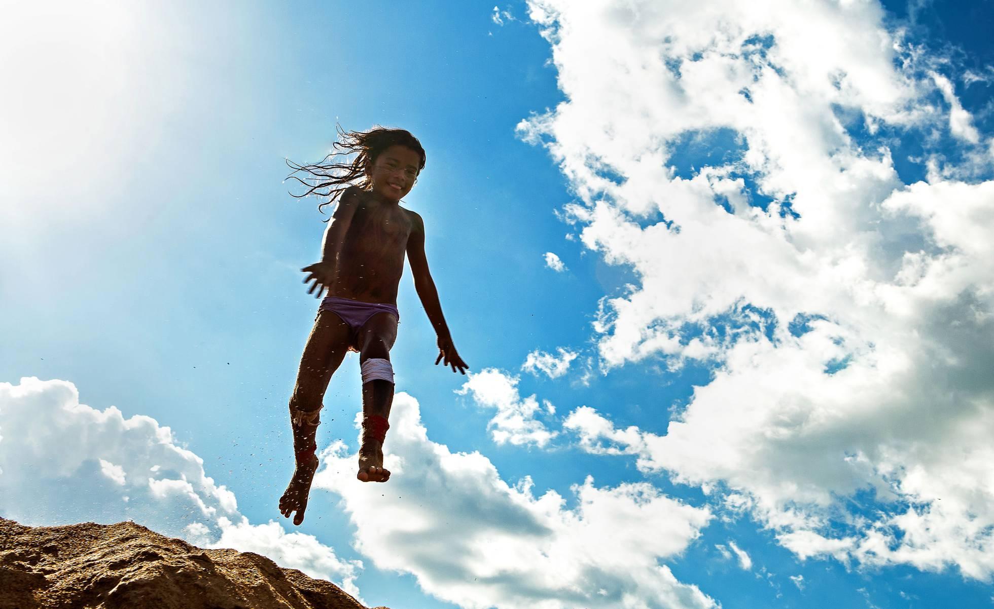 Alice Juruna, em fotografia de 2015, salta para mergulhar no rio Xingu. LILO CLARETO