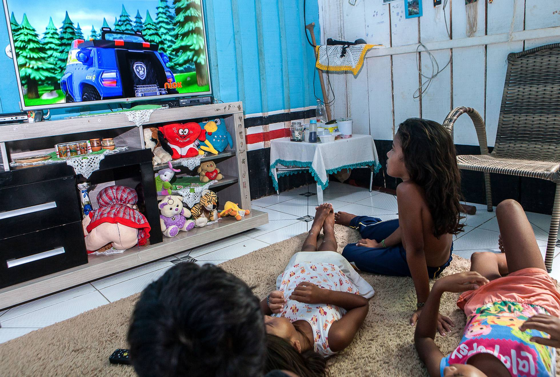 Em foto de 24 de março de 2017, Alice (sentada) assiste a desenhos na TV, hoje principal lazer das crianças indígenas, proibidas de se aproximar do rio. LILO CLARETO