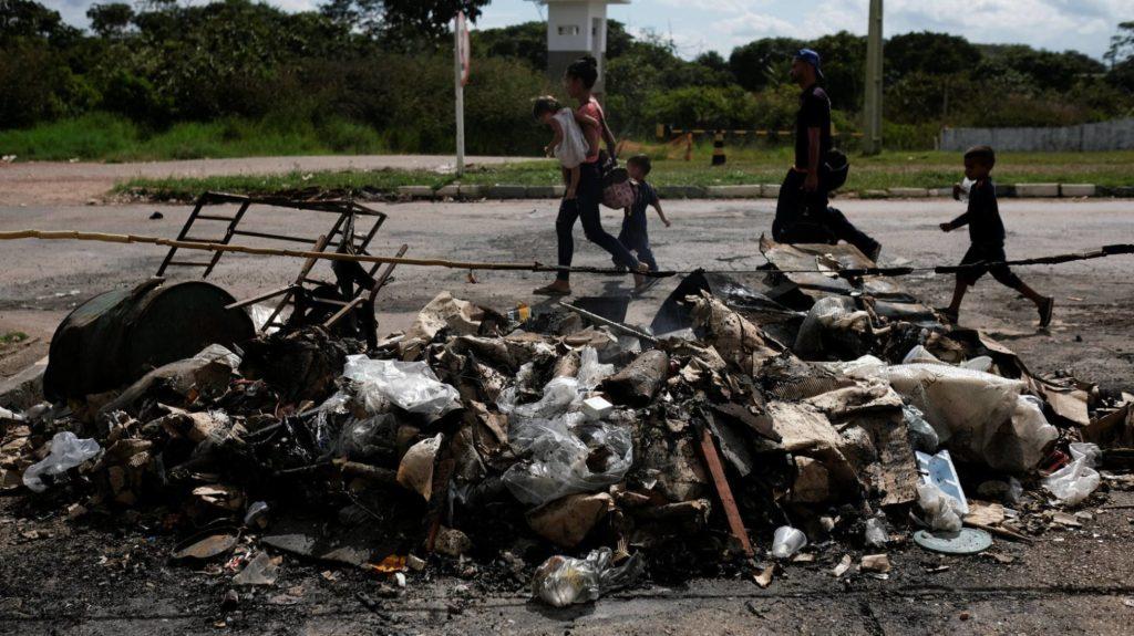 Uma família de venezuelanos passa pelos seus objetos pessoais incendiados por brasileiros na fronteira de Pacaraima (Roraima). NACHO DOCE REUTERS (Reprodução do El País)