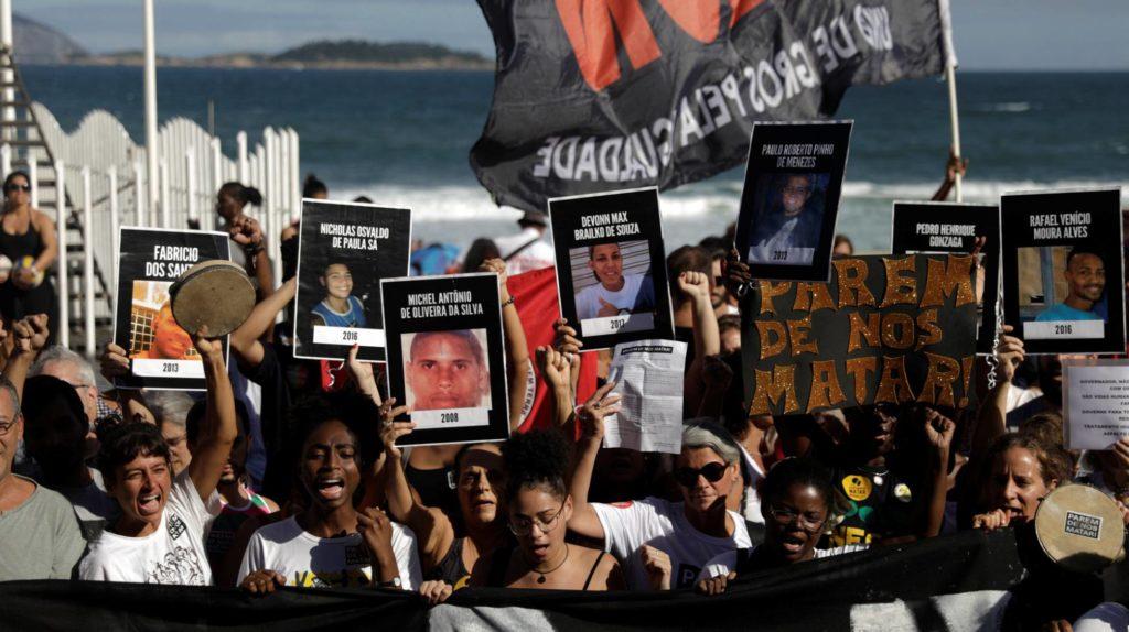 Habitantes de las favelas de Río muestran fotos de víctimas de violencia mientras participan en una protesta cerca de la playa de Ipanema en Río de Janeiro, Brasil, el pasado 26 de mayo. (Foto: Ricardo Moraes/Reuters/Reprodução do El País)