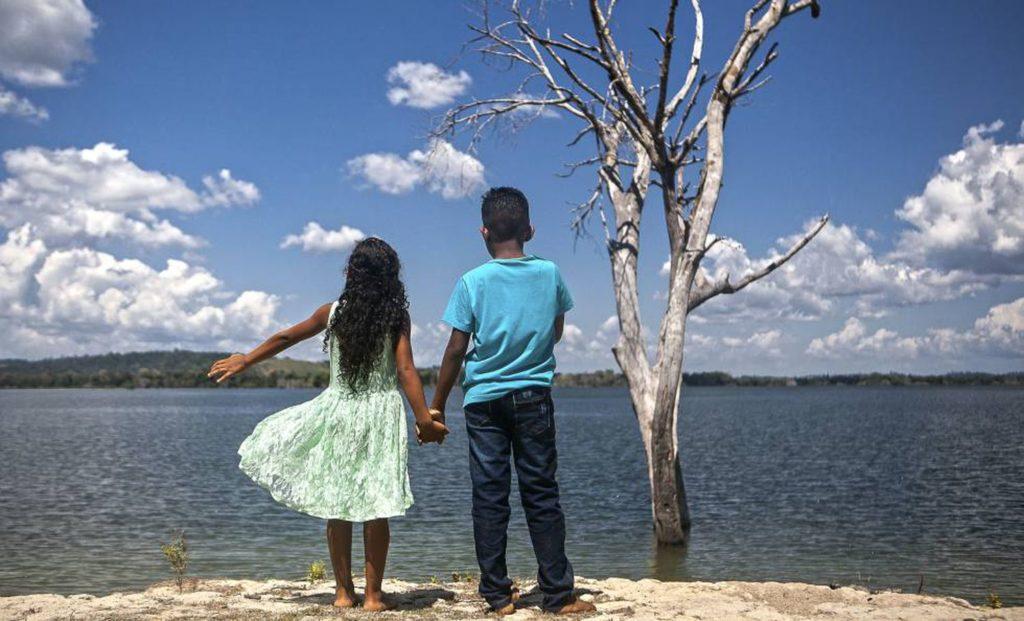A menina com nome de rua e o menino com nome de jogador de futebol, no reservatório da usina de Belo Monte, em Altamira (PA). (Foto: Lilo Clareto/Reprodução do El País)