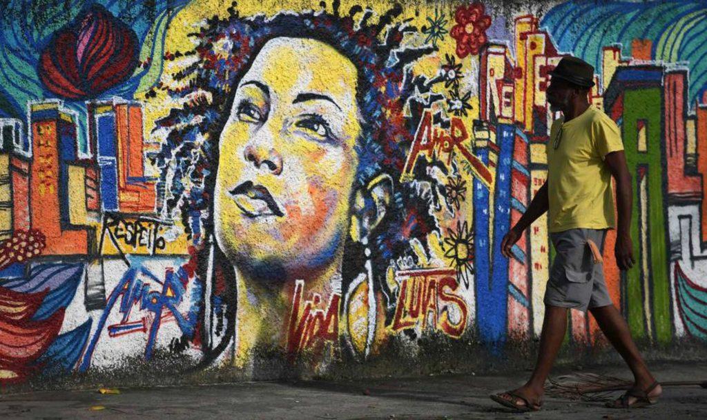 Homem caminha em frente a um mural de Marielle Franco, no Rio de Janeiro. (Reprodução do El País)