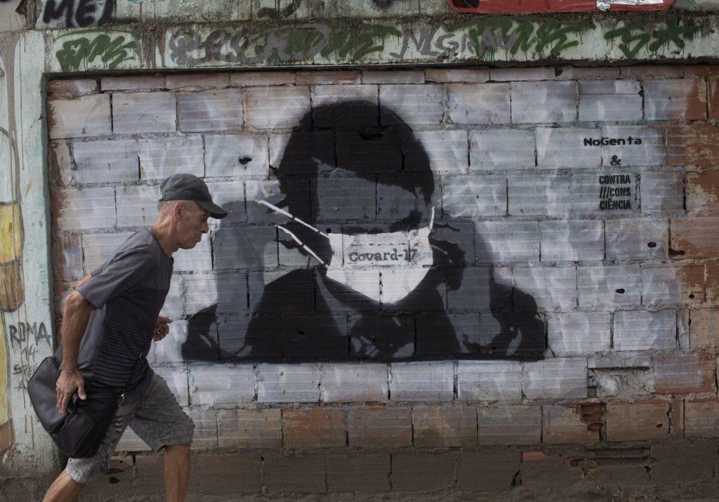 Um homem passa por um grafitti de Jair Bolsonaro durante a pandemia de coronavírus, no Rio de Janeiro, nesta terça-feira.SILVIA IZQUIERDO / AP (Reprodução do El País)