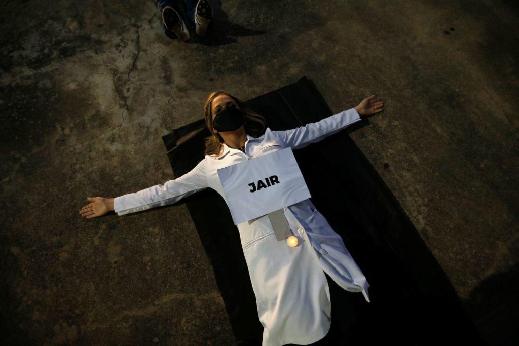 """Enfermeira protesta com cartaz em que se lê """"Jair"""", nome de um dos profissionais de saúde mortos pelo coronavírus no Brasil, na segunda.ADRIANO MACHADO / REUTERS (Reprodução do El País)"""