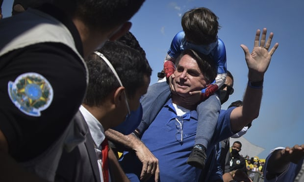 'Bolsonaro has hijacked the country's joy and creative power' ... Bolsonaro carries a boy on his back as he greets supporters in Brasilia on Sunday. Photograph: Andre Borges/AP (Reprodução do The Guardian)