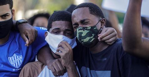 Dois jovens choram no enterro de João Pedro Matos Pinto, em São Gonçalo, no Río de Janeiro.ANTONIO LACERDA / EFE (Reprodução do El País)