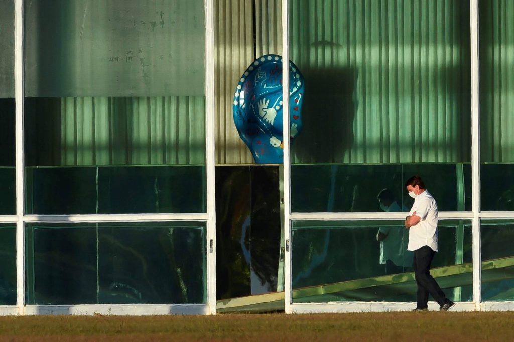 El presidente brasileño, Jair Bolsonaro, camina frente al Palacio Alvorada este lunes en Brasilia, Brasil.SERGIO LIMA / AFP (Reprodução do El País)