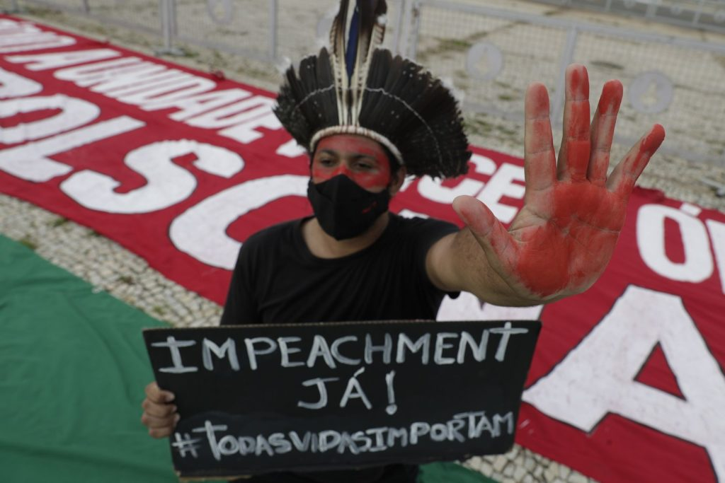 Manifestante protesta contra o presidente Jair Bolsonaro na frente do Planalto, no último sábado. ERALDO PERES /AP (Reprodução do El País)
