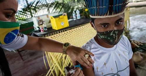 Una trabajadora del Distrito Sanitario Especial Indígena vacuna en la Amazonía. RAPHAEL ALVES / EFE (Reprodução do El País)