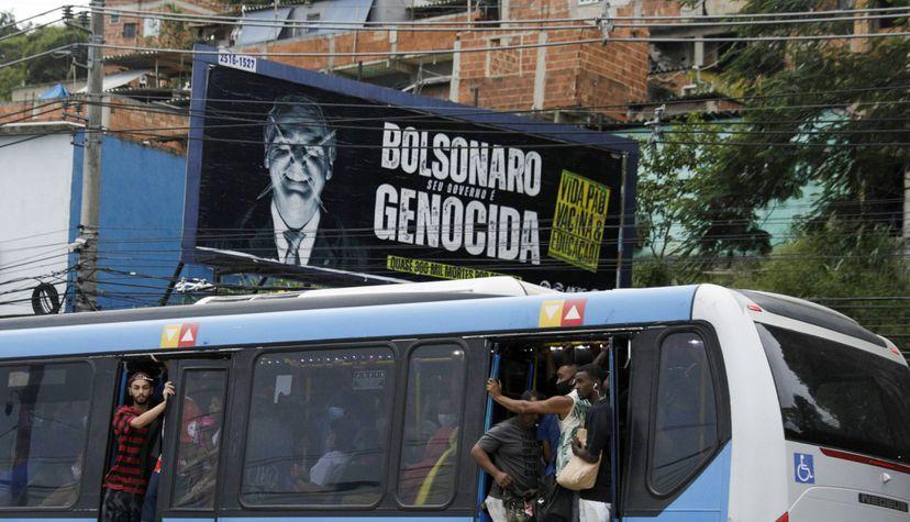 Passageiros circulam em ônibus lotado nesta terça-feira, no Rio de Janeiro, ao lado de outdoor crítico a Jair Bolsonaro. RICARDO MORAES / REUTERS (Reprodução do El País)