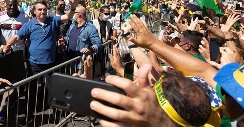 O presidente Jair Bolsonaro acena a apoiadores, aglomerados em plena pandemia de covid-19, em março. JOÉDSON ALVES/EFE (Reprodução do El País)